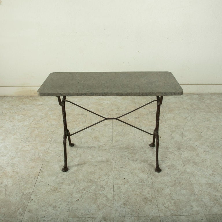 Originally used in a French brasserie during the early-twentieth century, this cast iron bistro table or cafe table features a solid grey marble top. Scrolled iron legs support the top and are joined by an X-stretcher that provides additional