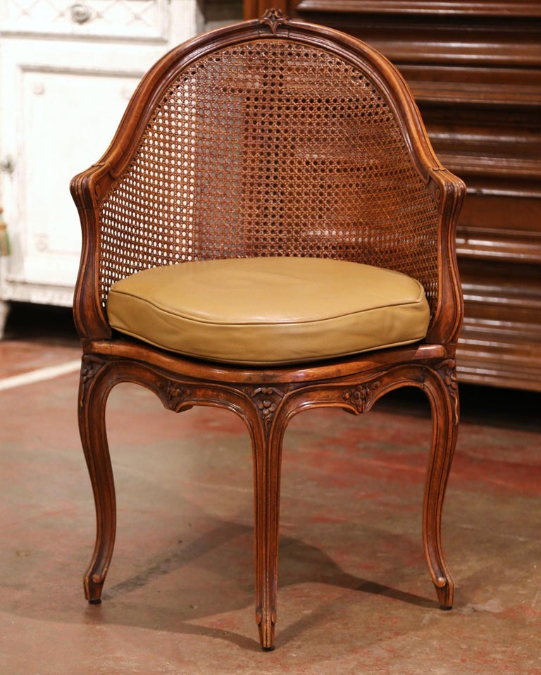 Decorate a study or office with this elegant antique desk armchair. Crafted in Provence, France, circa 1900, the corner chair has an arched cane back decorated at the top with floral motif. The traditional desk chair stands on four carved cabriole
