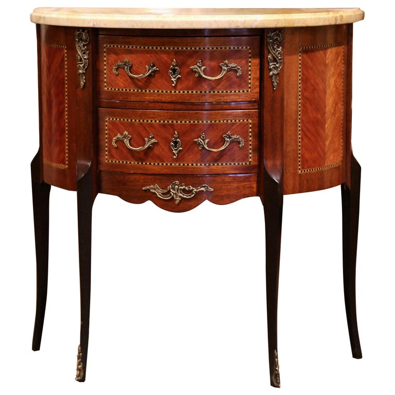 Decorate a living room with this elegant antique chest of drawers; crafted in France, circa 1920 and shaped as half-moon, the cabinet sits on cabriole legs with bronze caps over the feet. The fruitwood commode features two bombe drawers across the