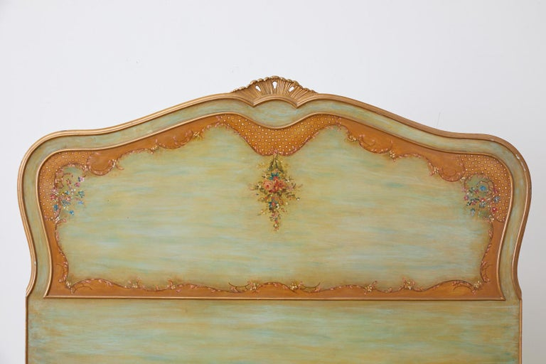 Gorgeous early 20th century lacquered bed decorated in the French Louis XV taste. Featuring a hand painted French green base with a parcel gilt finish. The headboard is detailed with delicate floral sprays with a shell crest. The foot board has