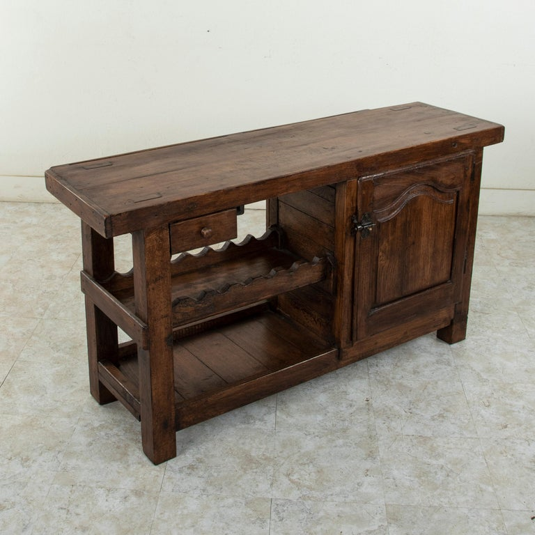 This early twentieth century French oak workbench is from the region of Normandy, France. Two slots at the back of the top once kept the artisan's tools close at hand. Its closed cabinet with single interior shelf, single drawer, and lower shelf