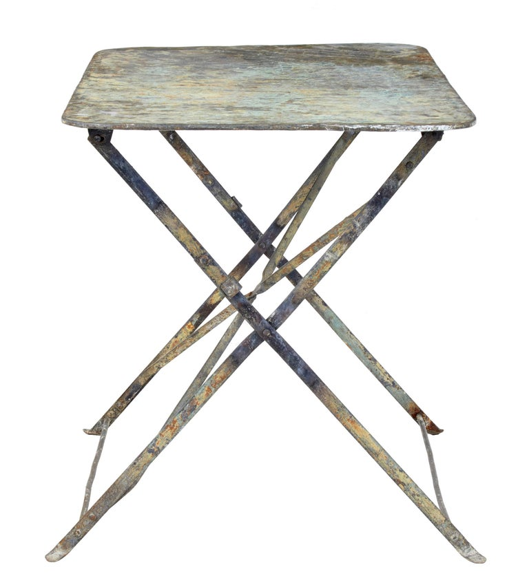 Lovely French country table, circa 1920.  Beautiful colored top which is now showing various layers of previous paint.  Fold up mechanism works smoothly to open out to a sturdy table.  Ideal for use in a garden room or outside.