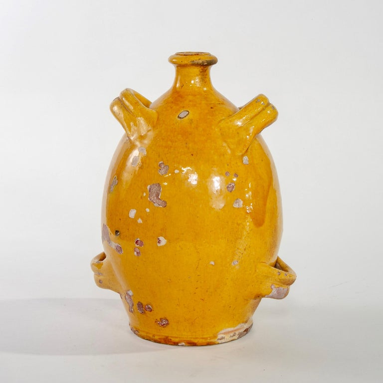 """Tall French ceramic jug has four handles, narrow neck and a mustard-gold color glaze, circa 1920s. Vessel stands just under 12"""" high and body has scattered flakes and chips to glaze."""