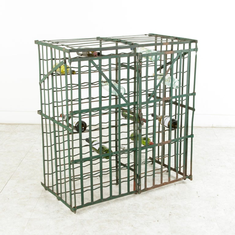 Originally used in a French wine cellar, this riveted iron wine cage from the early twentieth century holds up to 200 bottles and is painted in a dark green. The lock plate that slides over the ring where a padlock can be secured is marked Fer