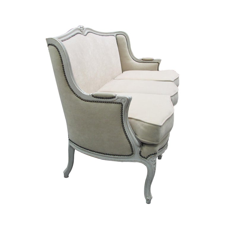 Very well-made French three-seat sofa with three separate seat cushions which have been newly reupholstered in a faux suede linen coloured fabric which is very resistant and easy to clean, circa 1900s. The frame and the elegant scrolled legs are