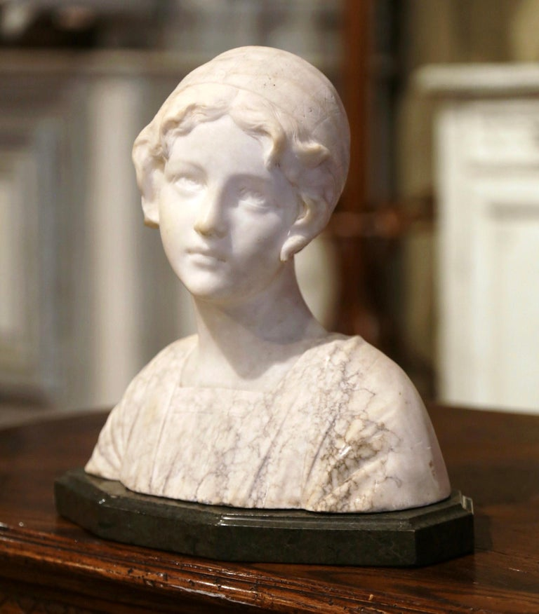 Decorate a shelf or desk with this antique two-tone and variegated marble bust. Created in France circa 1930 and rising on a separate flat green base, the sculpture features a young woman looking to the side, dressed in pre-20th century clothing and