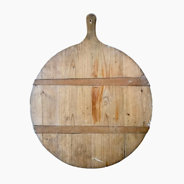 An early 20th century German pine breadboard, excellent for serving cheese, charcuterie, or anything else your guests desire.
