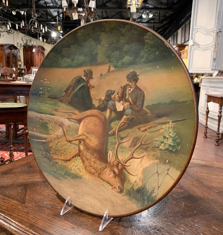 This large colorful platter was created in Germany circa 1920, round in shape, the black forest plate depicts a hand painted hunt scene featuring two hunters seated smoking pipes and eating, and two dogs in the background. The large trophy deer lays