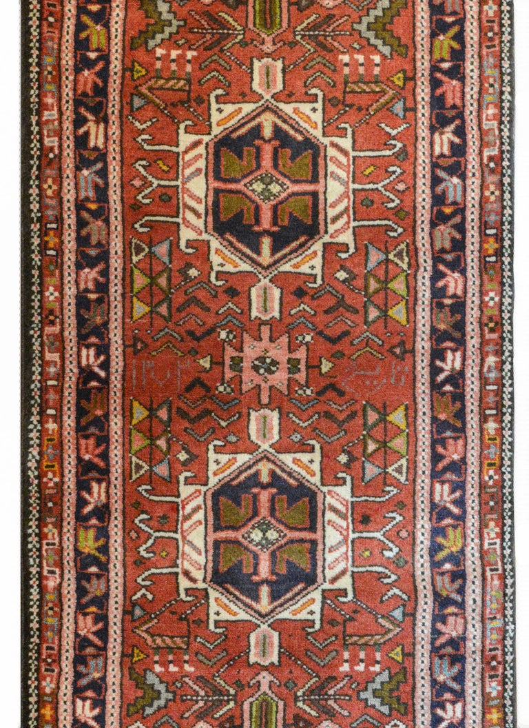 A wonderful early 20th century Persian Karadja runner with several stylized floral medallions woven in black, crimson, light blue, gold, and pale green amidst a field of more stylized flowers against a crimson background. The border is wonderful