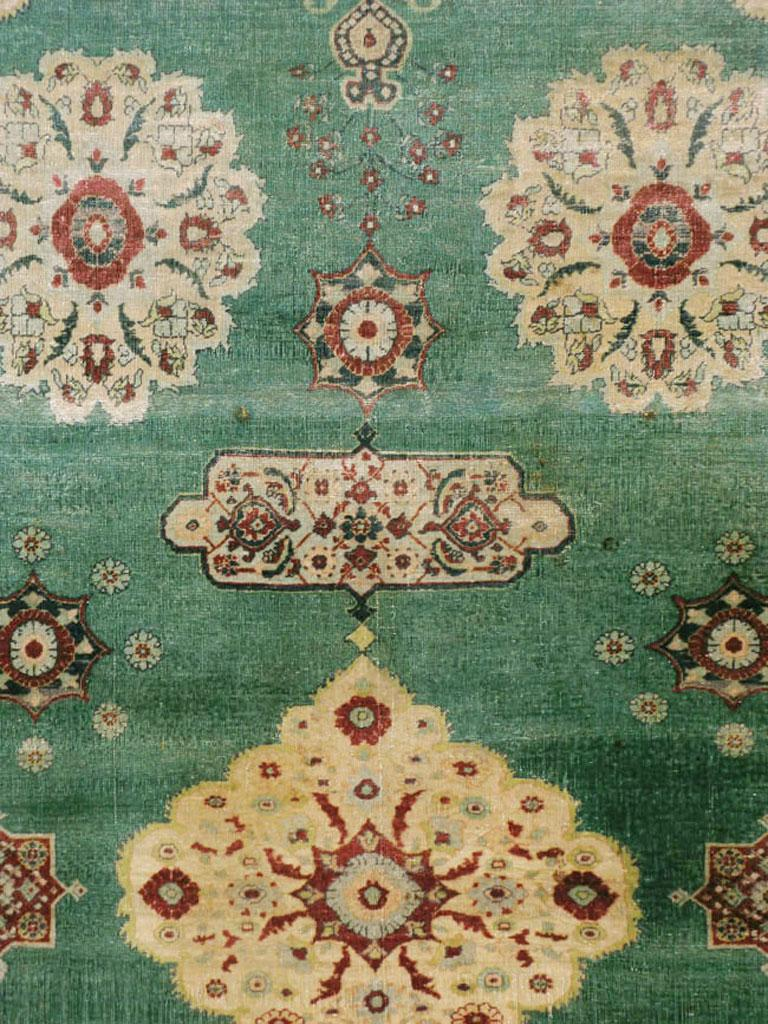 An antique Indian Agra carpet with a weathered appeal from the early 20th century. In the Persian Sultanabad-Mahal style, but with a green field instead of madder red, the gently scalloped straw central medallion pends cartouches and palmettes,
