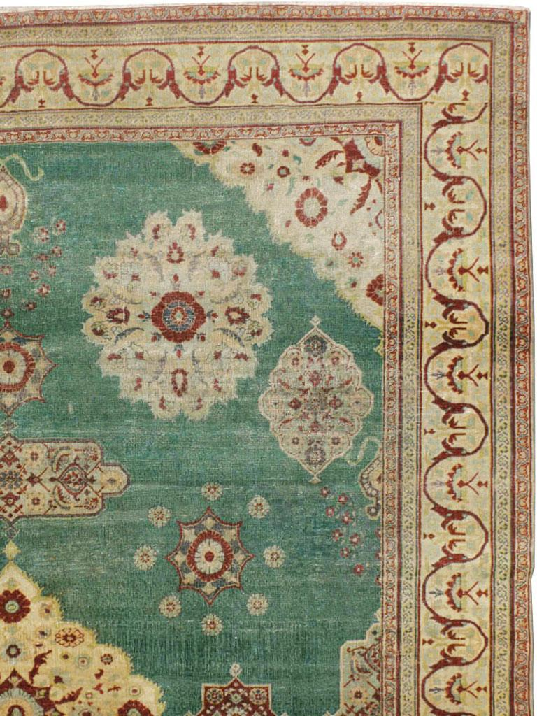Indian Early 20th Century Green, Red, and Beige Distressed Rug For Sale