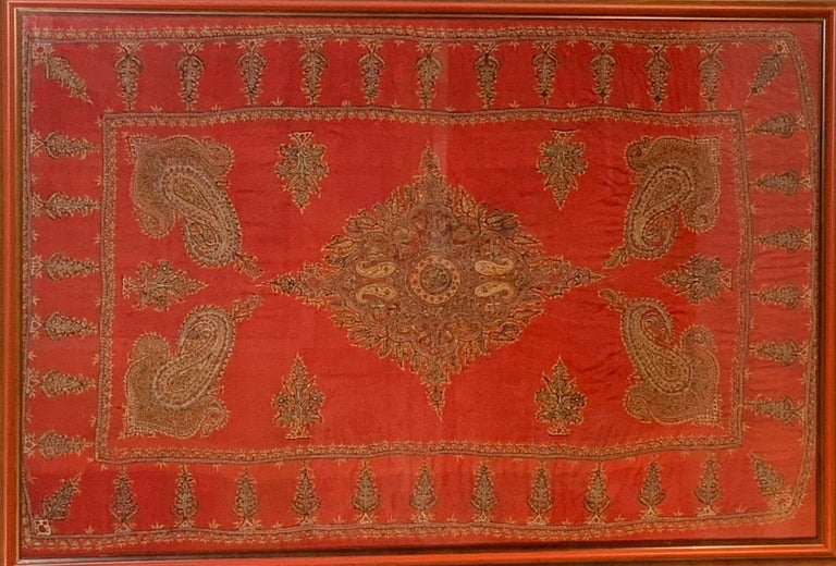 An exceptional early 20th century Kirman wool embroidered Suzani textile with a beautiful pattern of densely embroidered paisley pattern woven in myriad colors of thread surrounding a relatively empty field containing large four paisley shape, and