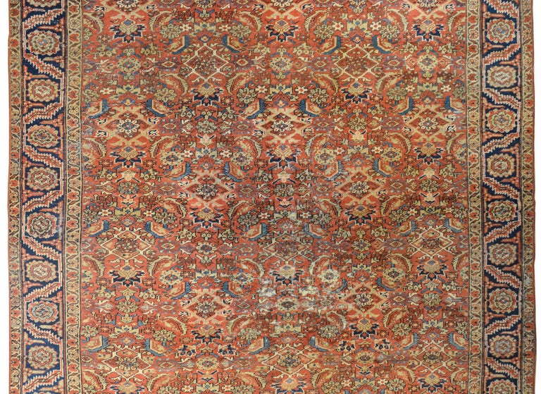 A beautiful early 20th century Persian Heriz rug with an all-over repeated floral pattern woven in light and dark indigo, cream, and pink colors on a coral colored background. The border is wonderful with a repeated large-scale floral and leaf