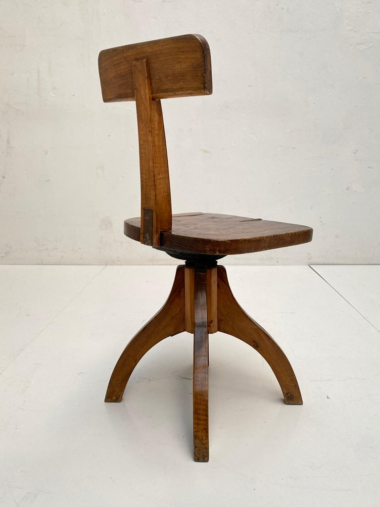 Early 20th century example of a swiveling desk chair in solid oakwood and cast iron hardware  Probably French manufacturing and made circa 1900s  Beautiful cast iron construction that holds a minimal