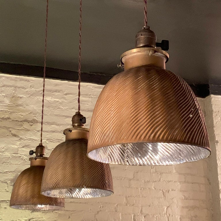 Early 20th century, industrial, factory pendant lights feature X-ray mercury glass dome shades with gold exteriors and silver interiors on brass paddle switch fitters, newly wired with 40 inches of braided cloth cord to accept up to 100 watt bulbs