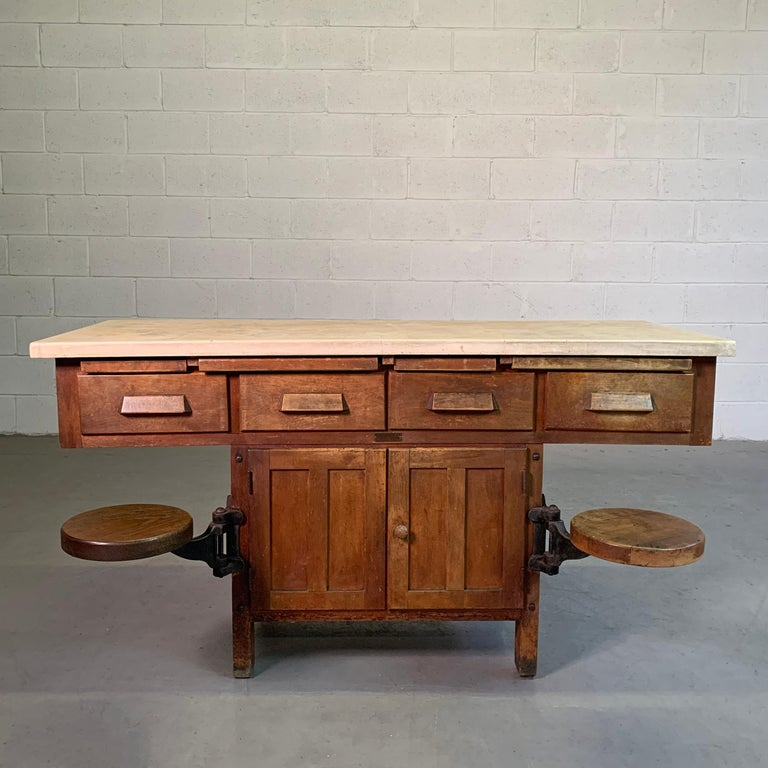 Early 20th century, Industrial, chemistry, laboratory workbench with concrete top, maple base and cast iron hardware features 2 swing-out seats, cabinet space, drawers and pull-out ledges. The seats are 10 inches diameter x 17.5 inches height with