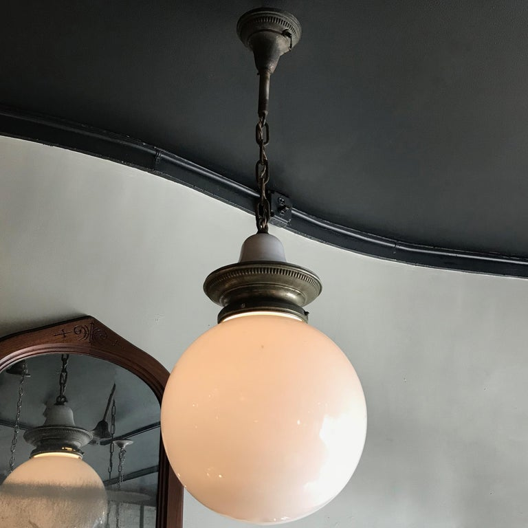 Early 20th century, industrial, library pendant light features a 14 inch milk glass globe shade with nickel-plated brass and porcelain enameled crown fitter, brass chain and canopy is wired to accept up to a 300 watt bulb. The overall height is 43