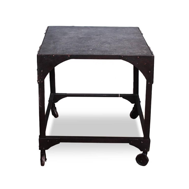 A vintage industrial low square table with rivet detailing and casters, USA, circa 1930.