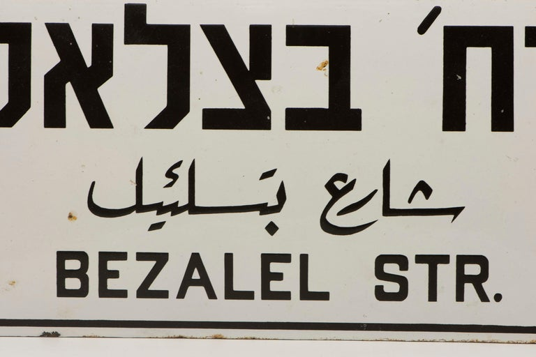 Three languages iron and enamel street sign, circa 1920. The sign was made to Honor Bezalel who was the chief artisan of the Tabernacle and was in charge of building the Ark of the Covenant, assisted by Aholiab. The three languages indicate the sign