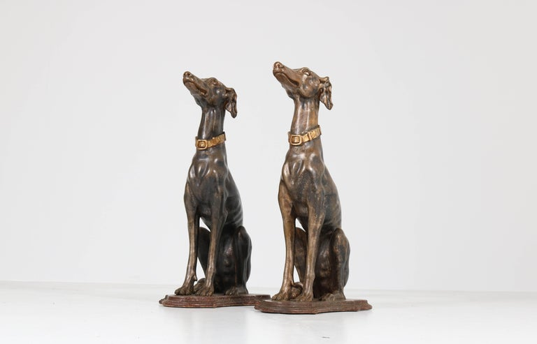 Stunning and elegant pair of early 20th century greyhound sculptures. The lean and muscular dogs are sitting quietly on the original faux-marble painted bases. Lacquered in grey with wonderful details such as their heads, ears and bodies as well