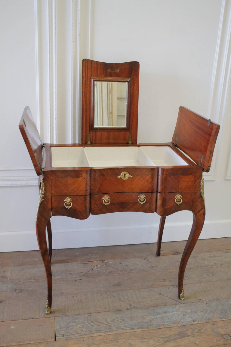 Early 20th century Italian inlaid vanity with original mirror and gilt bronze mounts and ring pulls. Drawers are finished with a dovetail, and has a white lining that can be removed easily. The vanity top centre opens by lifting straight up, then