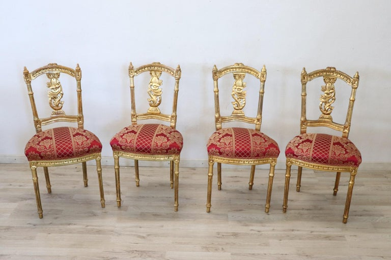 Series of four refined early 20th century authentic Italian louis XVI style chairs. These chairs are of extreme refinement made of carved wood with decorated back and completely covered in precious gold leaf. The session has been restored. The