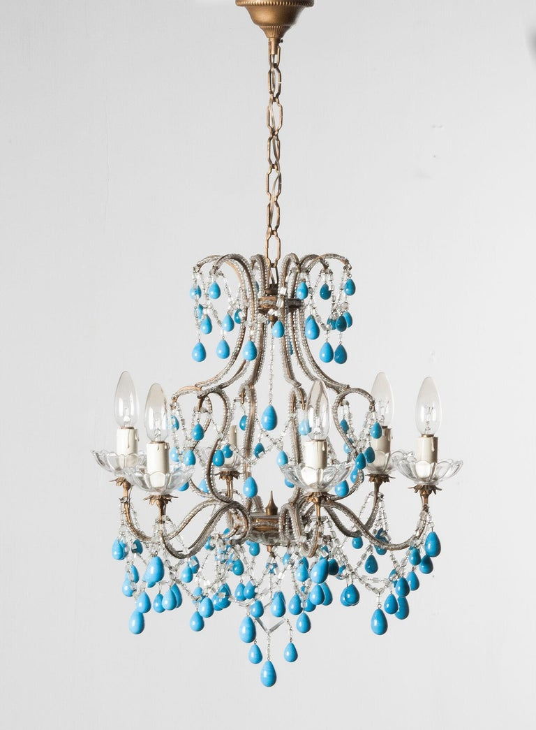 An early 20th century Italian beaded chandelier with blue opaline glass Murano drops. The structure have a birdcage shape, made of gilded brass. Crystal cut bobeches. Perfect for any room. Complete and working. Height including chain is 78 cm. Ø 45