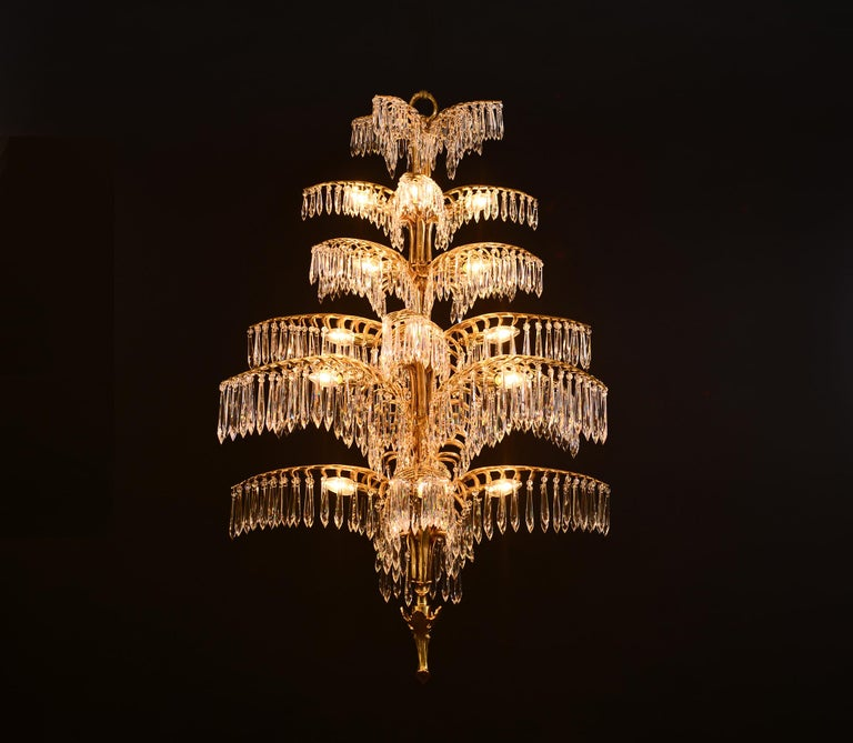 TMagnificent chandelier in solid casted brass. Extraordinary elaborate finishes. Rich hangings with hand-cut crystal glasses. Surface either brass, patinated, chrome et cetera In addition there is a Palme-wall-lamp available as well as a smaller