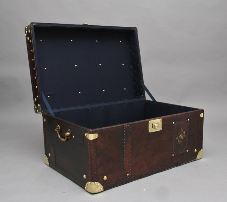 A fabulous early 20th century leather bound ex army trunk with brass straps and corners, copper studs and brass carrying handles on the sides, the trunk opens to reveal a nice dark blue lined interior, on the front of the trunk there is the