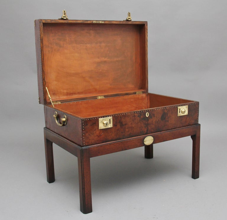 Early 20th century leather bound ex army trunk on stand with brass corners, copper studs and brass carrying handles on the sides, on the top of the trunk there is a regimental badge which belongs to the home counties, the hinged top opens to reveal