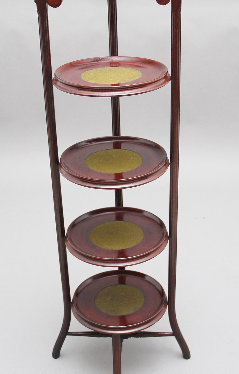 A decorative early 20th century mahogany four-tier cake stand, the four dish shaped tiers having green baize inserts, these are supported on a turned and fluted frame with outswept legs, the top of the cake stand is decorated with a turned finial,