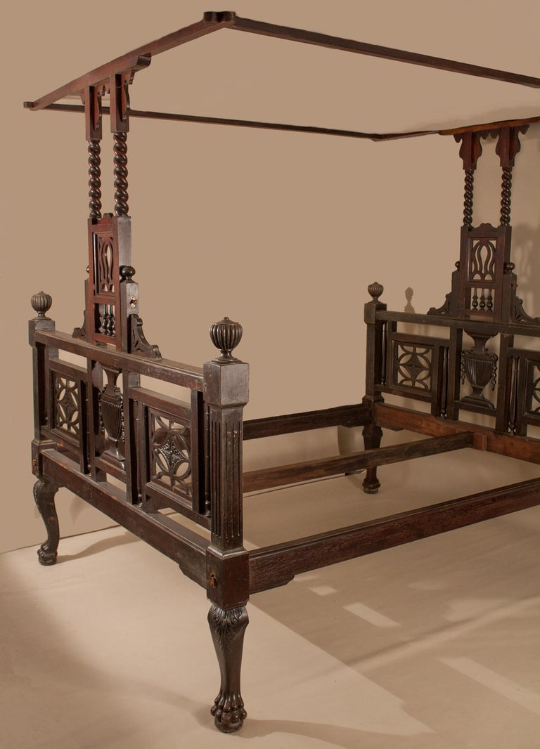 This circa 1900 hand-carved mahogany tester bed is a treasure from Kolkata, once the capital of British India. The head- and footboards are mirror images, with Grecian urns carved in the center  and panes with carved flowers on both sides. The