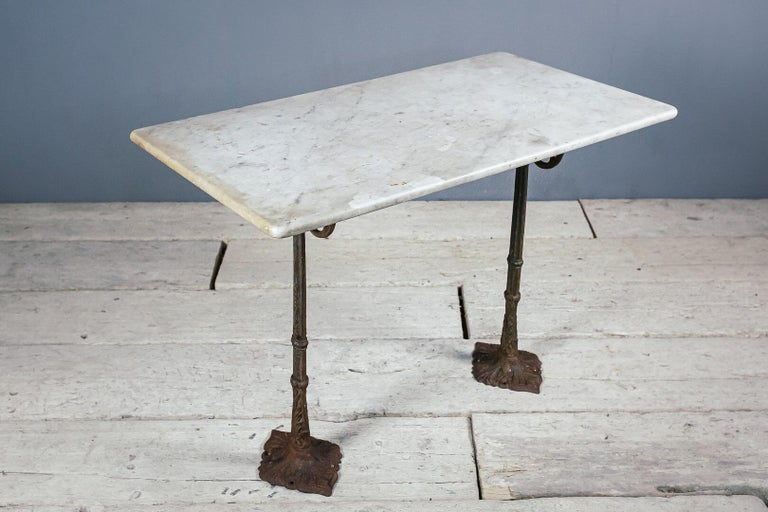 Cast iron and marble bistro table, remnant paint to the cast iron base and a good patina to the old marble top. This table comes as three pieces, two legs and the top which sits on top. The bases were historically fixed to the floor and ideally
