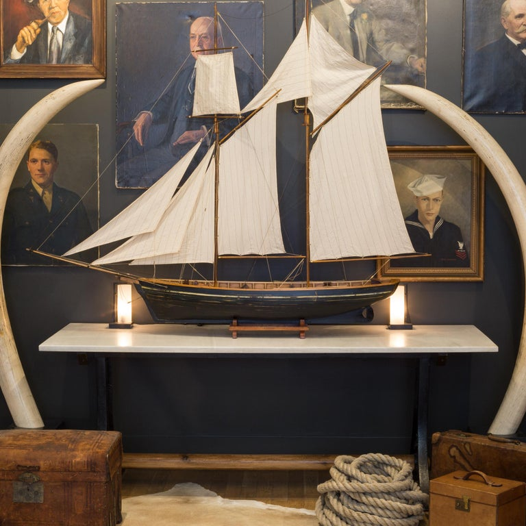 Large wooden ship model with original sails and stand. Brass accents are on the tips of the masks and throughout the ship.  Possibly repainted at one point but unsure.