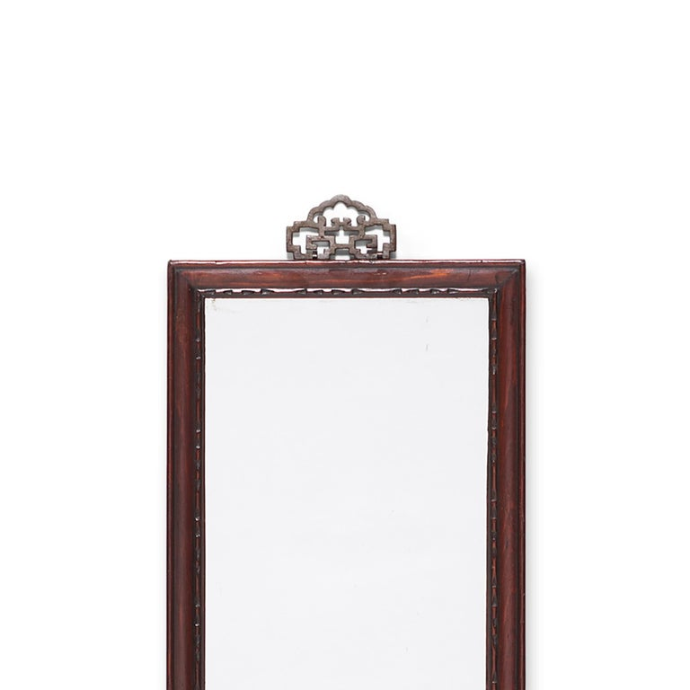 This early 20th century mirror is crafted of hand carved pine and once hung on the wall of a Qing-dynasty home, perhaps in a ladies sleeping quarters. Subtle notches pattern the frame's finely beaded edges and brass hardware adorns the top, formed