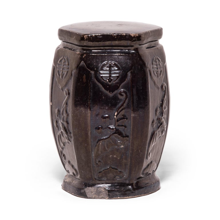 This early 20th century garden stool from China's Hebei province has the proportions of a traditional drum-form stool, but its hexagonal shape and waisted ends make it an unusual find. Although the dark glaze appears perfectly even from afar, a