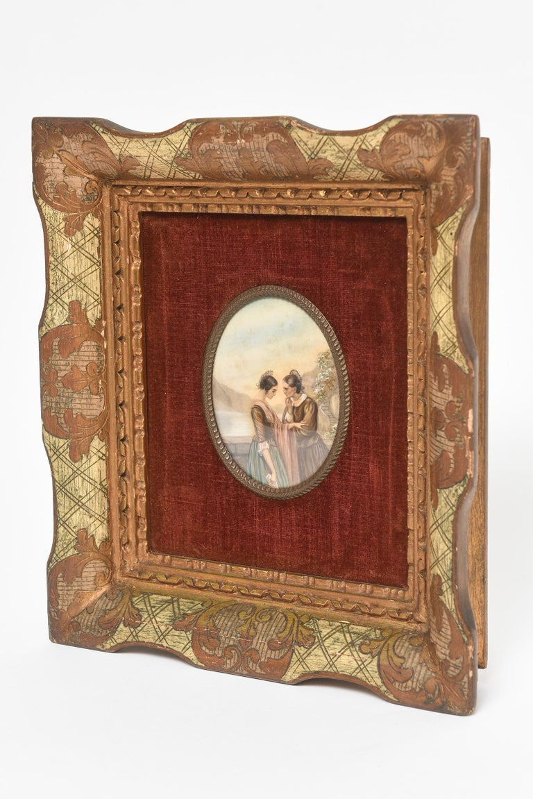 Early 20th century painting on celluloid of the women by the water having a deep conversation. It looks as if the older one is advising the younger one. The painting is set is a giltwood frame with a burgundy velvet background.