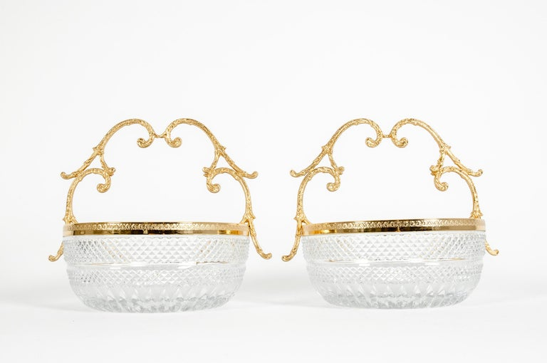 Early 20th century pair of cut crystal with gilt bronze handled design detail bowls / pieces. Each one Features a cut crystal diamond pattern body with gilt bronze rim, having scroll handles. Each one is in great condition. Minor wear consistent