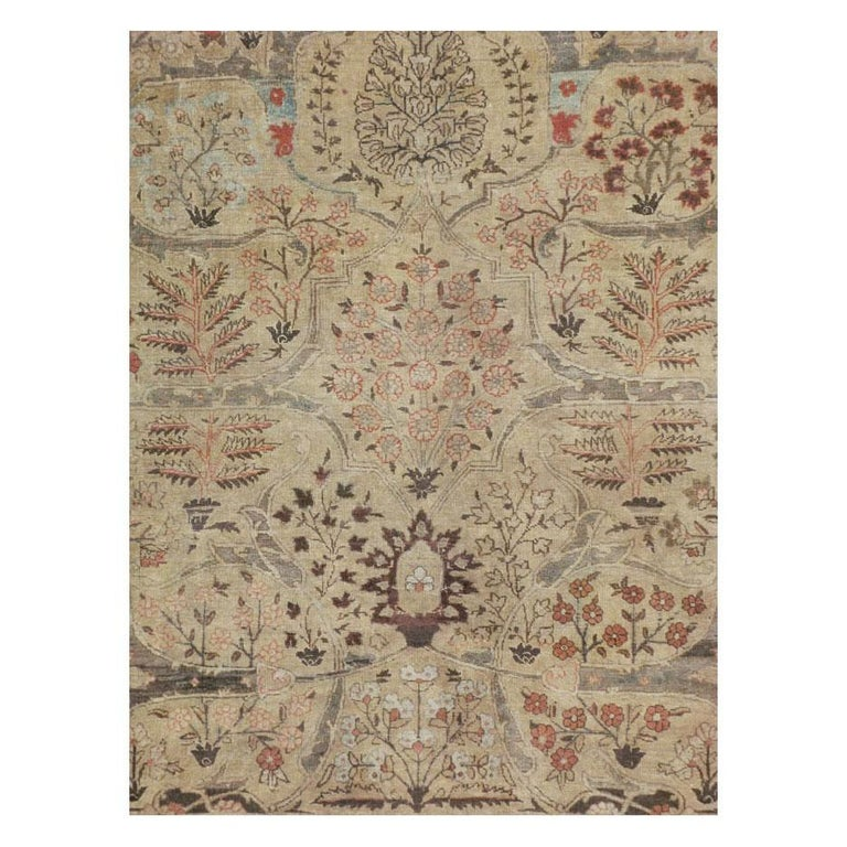 An antique Persian Tabriz small room size carpet handmade during the early 20th century. The floral design is split evenly along each side of the central axis over a light brown field decorated with a large-scale arabesque in slate grey. More