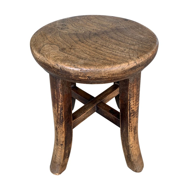 An early 20th century petite Chinese elmwood stool with legs ending in cute flared feet. The top is one solid piece of wood with rounded edges. Also serves as a small drinks table next to a low sofa or chair.