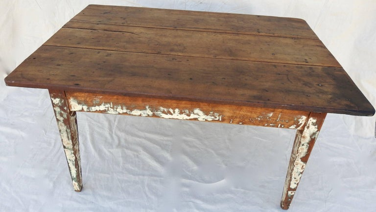 Chippy white paint on the legs and sides of this walnut farm table will be perfect for your farmhouse style! The simple, tapered legs support the smooth walnut top with rounded edges. The worn finish will give it a warm feel in your home. Square