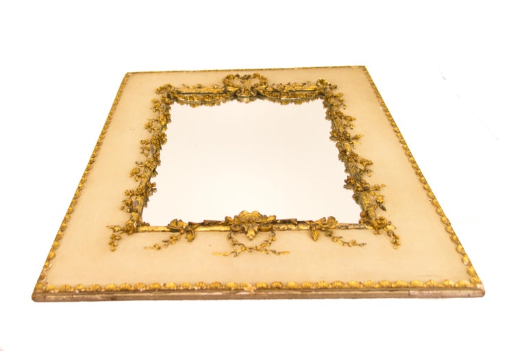 This exquisite antique trumeau Rococo or Louis XV style picture or mirror frame on white painted wooden panel is decorated with golden garlands of flowers and leaves, perimeter decorated with small golden shell ornaments. The frame has a newly