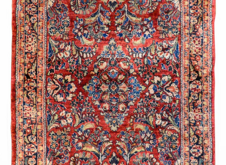 A gorgeous early 20th century Persian Sarouk rug with an all-over pattern containing several large flower clusters woven in indigo, pink, green, and white, against a dark cranberry background. The border is wonderful with a central floral patterned