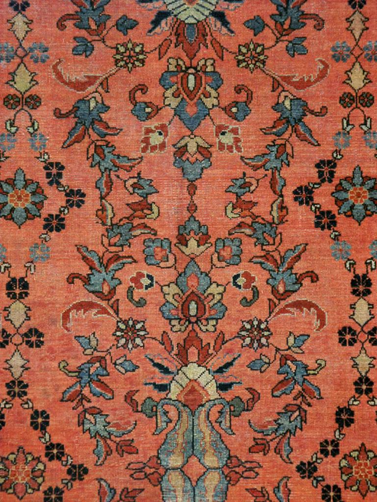 """An antique Persian Malayer carpet from the early 20th century. Influenced by the detached floral spray patterns of """"American-style"""" Sarouks, the scarlet red ground has a design of lozenges formed of chains of small rosettes. The excellent border"""