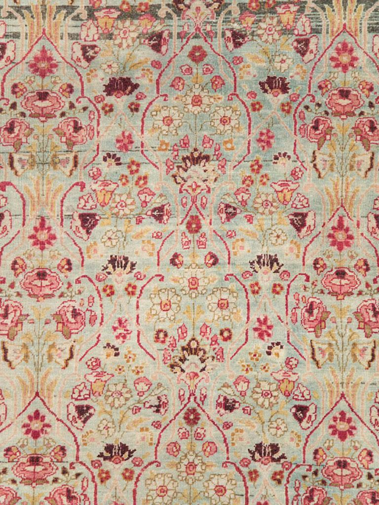 An antique Persian Mashad room size carpet from the early 20th century with an intricate Millefleur pattern in both the seafoam green field and ruby red border.  Measures: 8' 6