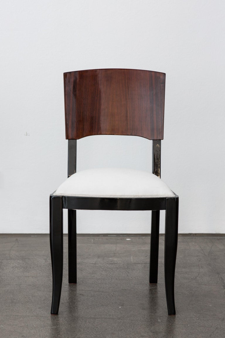 A set of six sublimely crafted Art Deco dining chairs manufactured around 1935 in France. The wooden legs are lacquered in black and the backrest is veneered with polished macassar, furthermore, the seat is wallpapered with white linen and the