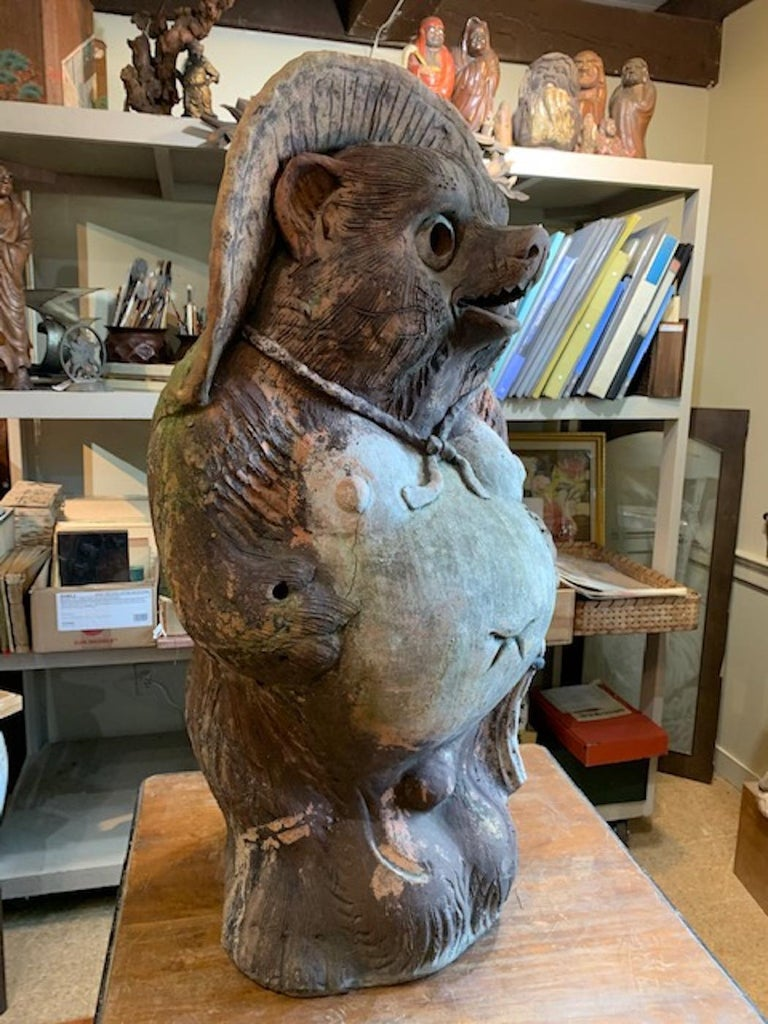 This Tanuki was made is Shigaraki and was used in front of an old Kyoto noodle shop.  Tanuki is a magical shape shifting badger that is believed to bring good fortune if placed in front of ones business or home. The log book that hangs from his