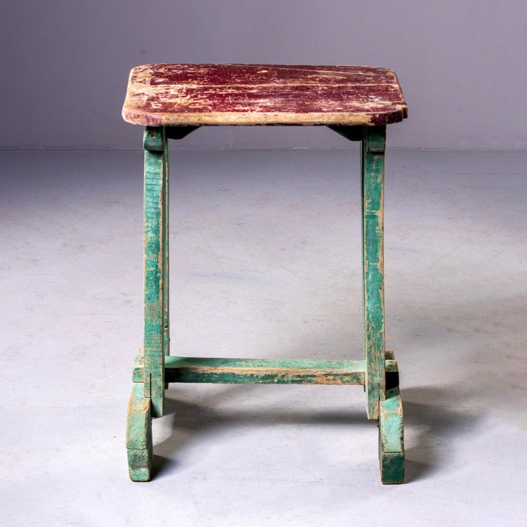 Painted wood side table found in England, circa 1900s. Original red paint on table top and green paint on base. Unknown maker.