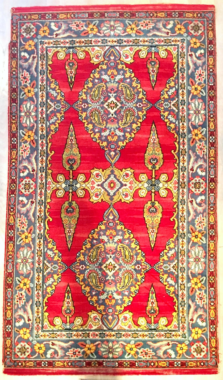 20th Century Classic Silk & Wood Paisley And Floral Blossom Indian Motif hand woven rug. Features, a vivid red ground with amethyst border accented by chartreuse, pink, white, yellow, and several shades of blue. Most likely from India. Measures: 3