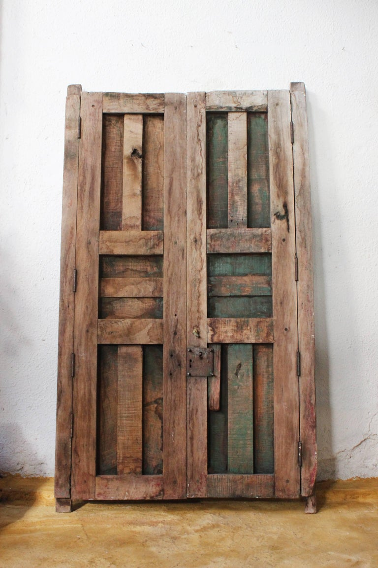 An early 20th century medium sized solid mesquite pair of doors found in Western México, the wood has fabulous cracking, great for many different applications such as a headboard, wall hanging, kitchen pot rack or just a backdrop layer in an